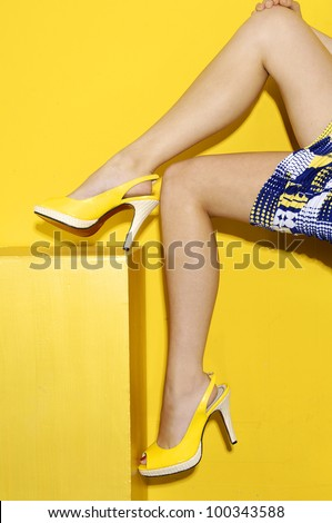 young girl sitting on cubes-yellow background