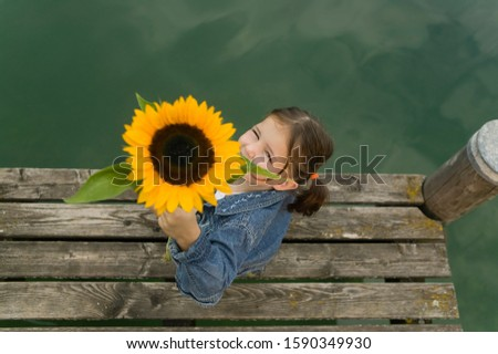 Young girl sitting on pier at lake with sunflower