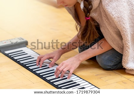 Photo of Young girl sitting on room floor at home and playing on folding piano keyboard. Interest activity on self-isolation. Concept keep of healthy lifestyle, wellness during pandemic. Image with soft focus.