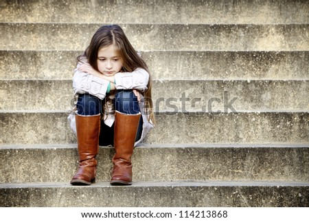 stock photo : Young girl sitting on steps and daydreaming.