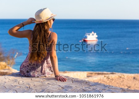 Young girl sitting on the coast looking to the boat at azure sea, Sharm El sheikh, Egypt #1051861976