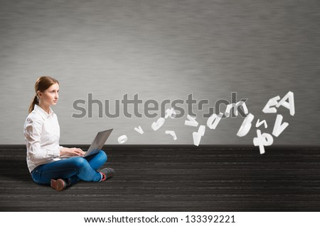 young girl sitting on the floor with a laptop from which emerge the signs and symbols