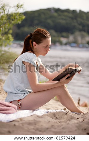 Young girl sitting on the riverside reading the book