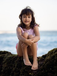 Young girl sitting on the rock near the ocean and smiling. Happy childhood. Spending time on the beach. Cute little girl. Vacation in Asia. Summer concept. Pandawa beach, Bali, Indonesia