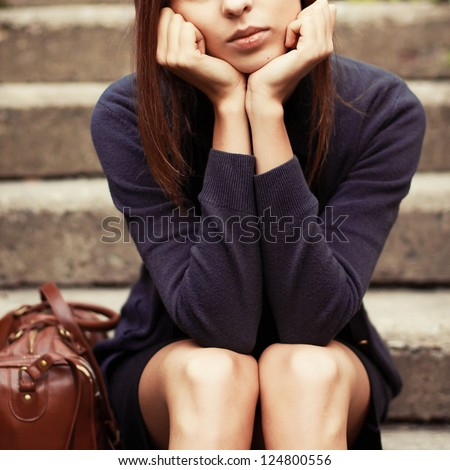 Young girl sitting on the stairs alone and waiting for smth. Outdoor vintage portrait. - stock photo