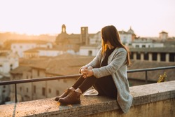 Young girl sitting on the top of the building overlooking the city with a beautiful sunset