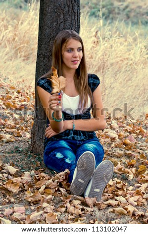 Young girl sitting on the yellow leaves under tree