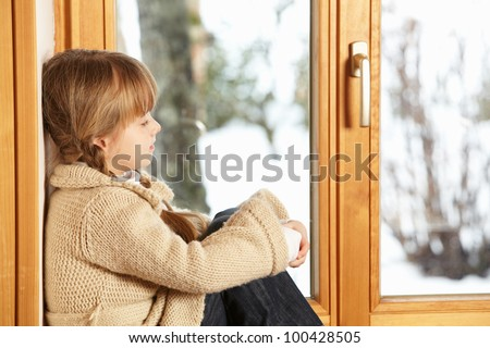 Young Girl Sitting On Window Ledge Looking At Snowy View