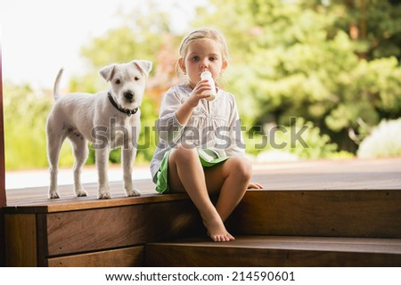 Young girl sitting on wooden steps with her dog eating doughnut