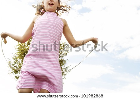 Young girl skipping in the park with a rope. - stock photo