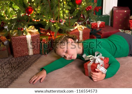 Young girl sleeping in front of the christmas tree holding her gift