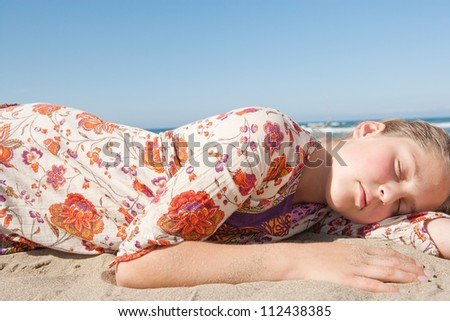Young girl sleeping on a golden sand beach while wearing a floral summer dress, relaxing. - stock photo
