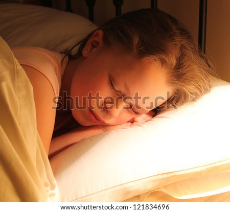 Young girl sleeping under the glow of her bedside lamp - stock photo