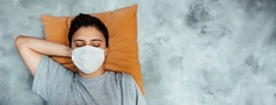 young girl sleeping yellow pillow gray background medical mask prevention.