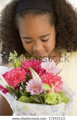 Young Girl Smelling A Bouquet Of Flowers