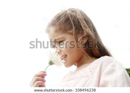 Young girl smelling white daisy flower against the sky, smiling.