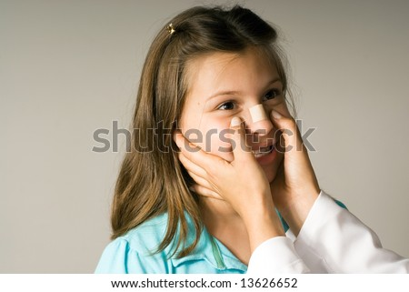 Young girl smiles while a band-aid is applied to her nose. She is happy to be taken care of. Horizontally framed photograph