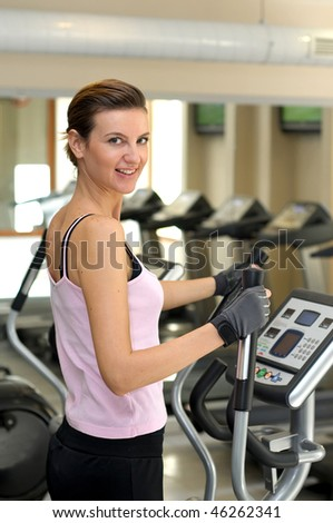 Young girl smiling and about to work out at the Gym