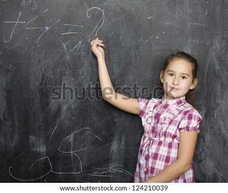 young girl smiling at blackboard with chalk