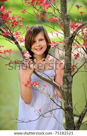 Young girl smiling outdoors by flowering dogwood tree