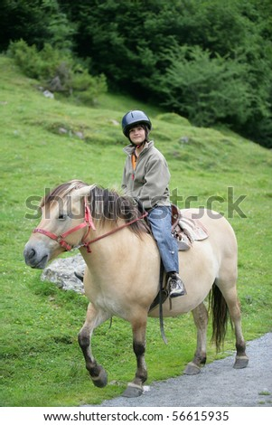 Young girl smiling sitting on a pony