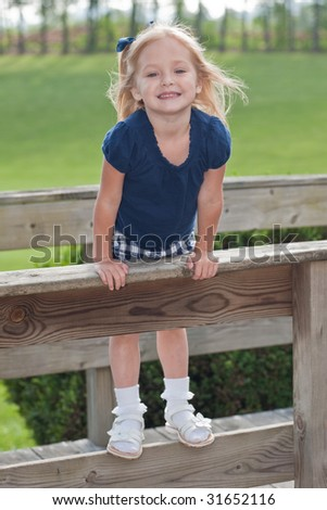 young girl smiling while standing on fence