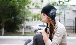 Young girl smoking cigarette outdoors