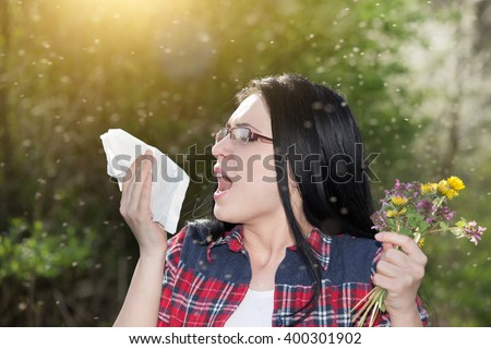 Young girl sneezing and holding paper tissue in one hand and flower bouquet in other. Allergies concept