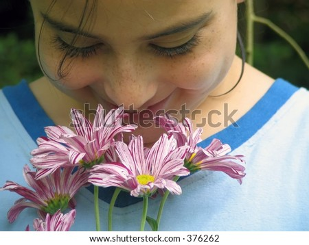 Young girl sniffing flowers