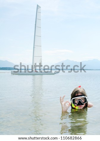 Young girl snorkeling in sea against her sail boat.