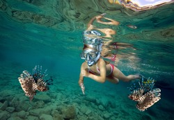 Young girl snorkeling with lionfish