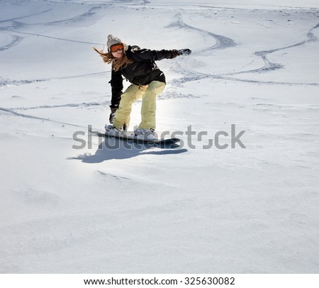 Young girl snowboarder in motion on snowboard in mountains