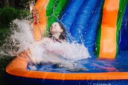 Young girl splashing into the bottom of a water bouncy slide.