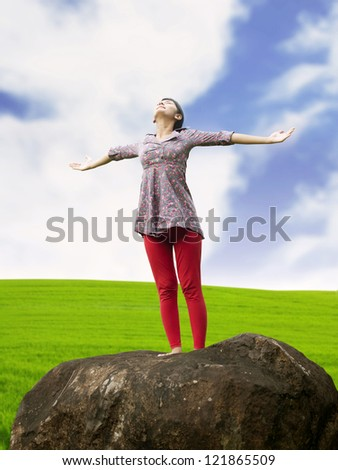 Young girl spreading hands with joy and inspiration facing the sky