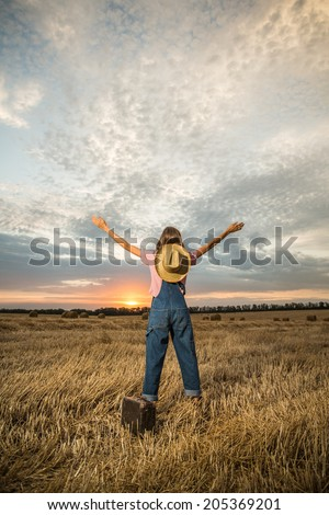 Young girl spreading hands with joy and inspiration facing the sun. Happy woman with hands up on sunset background. grain added