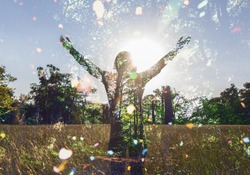 Young girl spreading hands with joy and inspiration facing the sun,sun greeting,freedom concept, nature lover ,spirit of forest