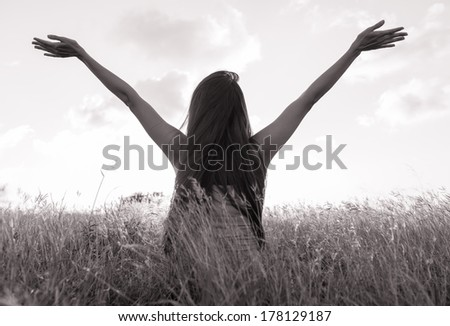 Young girl spreading hands with joy and inspiration. Freedom concept.
