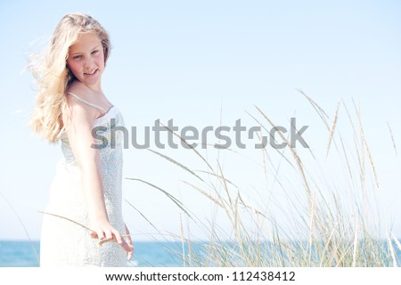 Young girl standing against a blue sky with long grass by the sea, turning and touching the grass.