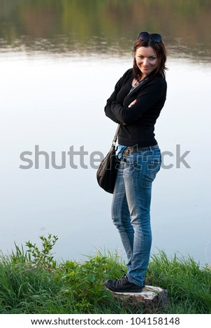 Young girl standing by the lake