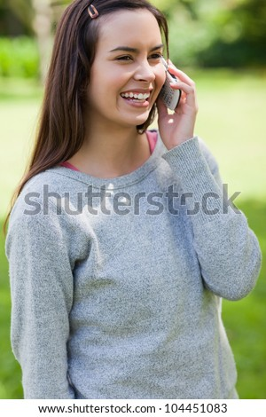 Young girl standing in a parkland while talking on the phone and laughing