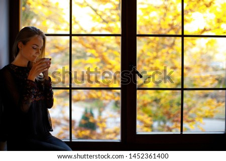 young girl standing near huge window with forest background and drink coffee, tea. autumn sadness concept.  vacation in mountains in autumn. loneliness concept  #1452361400
