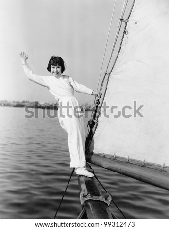 Young girl standing on a sailboat and waving