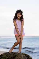 Young girl standing on the rock near the ocean and smiling. Happy childhood. Spending time on the beach. Cute little girl. Vacation in Asia. Summer concept. Pandawa beach, Bali, Indonesia