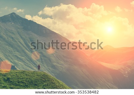 Young girl standing on the top up against the sky and mountain