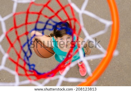 Young girl standing with basketball under hoop