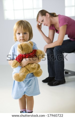 Young girl standing with teddy bear and looking at camera. Her mother sitting behind and thinking. Focused on young girl. - stock photo
