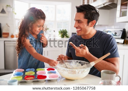 Young girl stands at the kitchen table making cakes with her father, tasting the cake mix, close up
