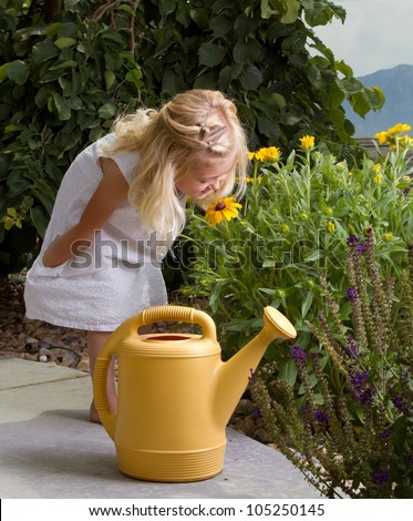 young girl stopping to smell flowers while watering them