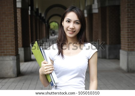 young girl student holding book on campus