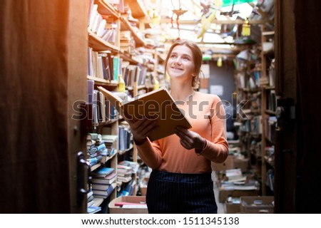 young girl student reads a book in the library, a woman likes to read a lot, she is looking for literature on bookshelves, knowledge is power, concept
